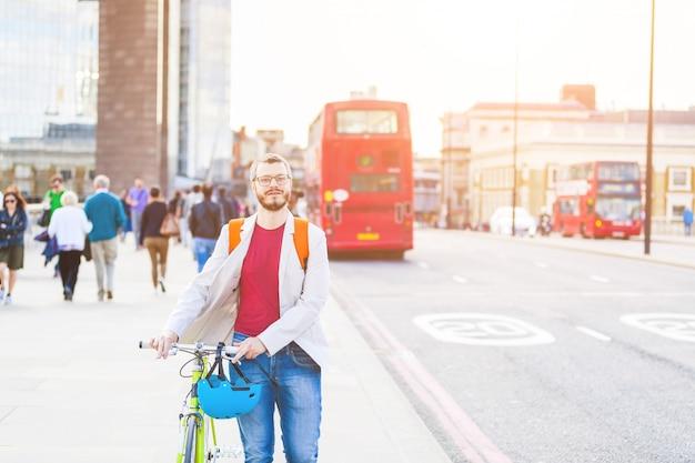 Hippie-mann, der auf london-brücke geht und sein fahrrad des örtlich festgelegten gangs hält