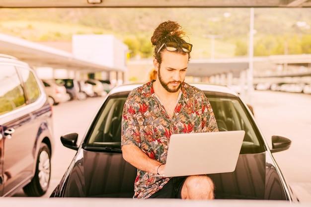Hippie mit dem laptop, der auf autohaube sitzt