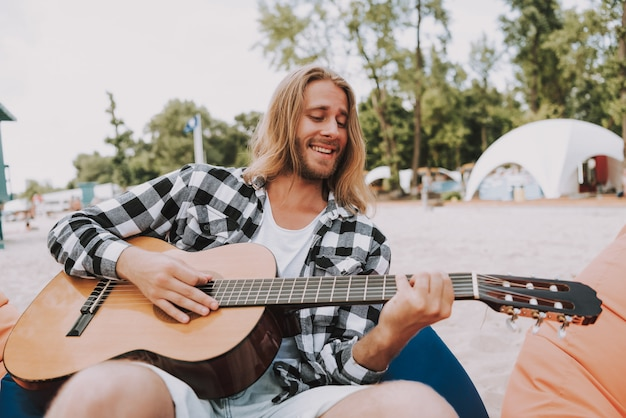 Hippie-musiker, der akustikgitarre auf strand spielt