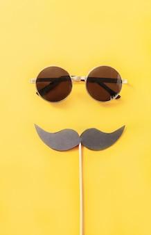 Hippie-sonnenbrille und lustiger schnurrbart auf gelb