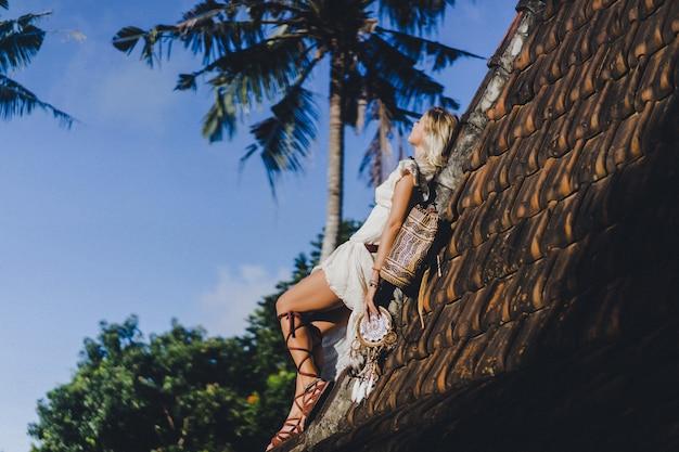 Hippiemädchen mit langen blonden haaren in einem kleid auf dem dach.