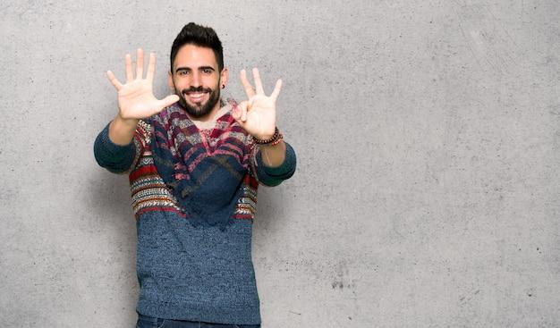 Hippiemann, der acht mit den fingern über strukturierter wand zählt