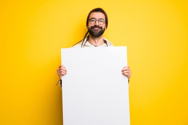 Hippiemann mit den dreadlocks, die ein leeres plakat für einfügen ein konzept halten