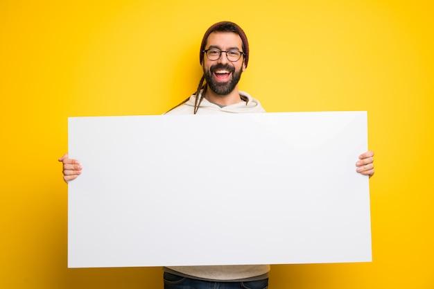 Hippiemann mit den dreadlocks, die ein plakat für einfügen ein konzept halten