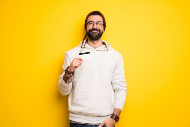 Hippiemann mit den dreadlocks, die eine kreditkarte halten