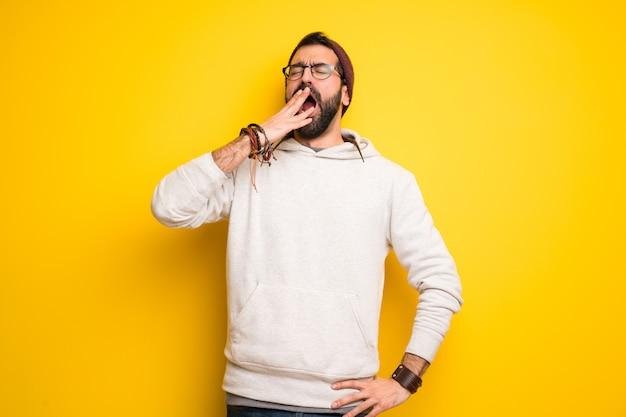 Hippiemann mit dreadlocks, die mit offenem mund mit der hand gähnen und den mund bedecken