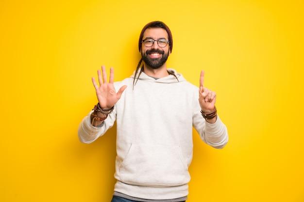 Hippiemann mit dreadlocks, die sechs mit den fingern zählen