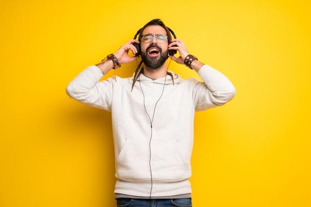 Hippiemann mit dreadlocks hörend musik mit kopfhörern
