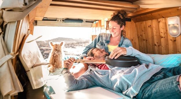 Hippiepaar und hund, die zusammen auf weinlesetransportertransport bei sonnenuntergang reisen