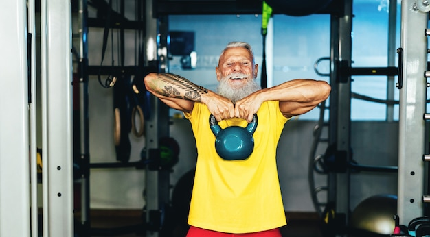Hipster älterer mann, der im fitnessstudio trainiert