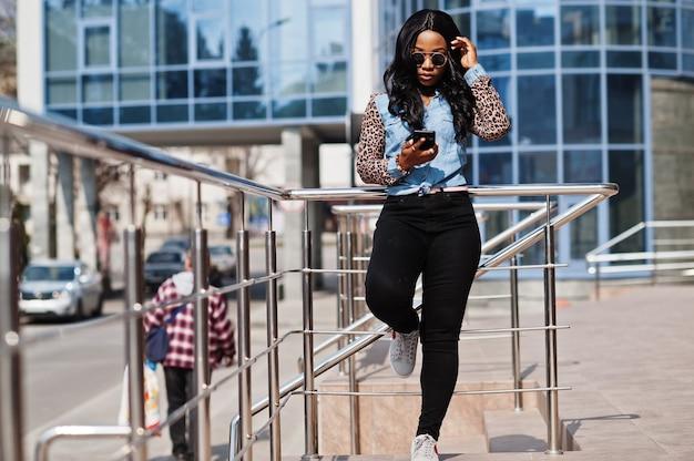 Hipster-afroamerikanermädchen mit sonnenbrille, jeanshemd mit leopardenärmeln, handy halten und auf der straße gegen modernes bürogebäude posieren.