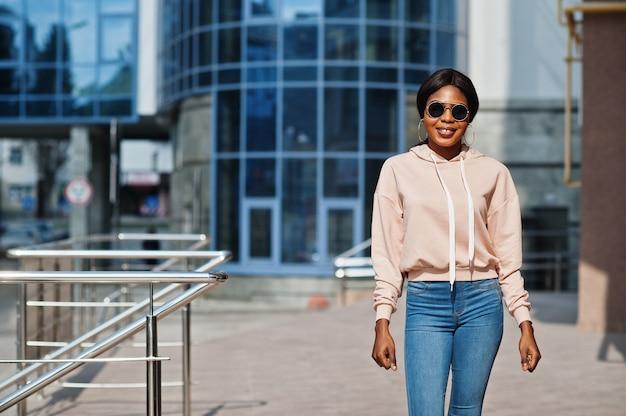 Hipster afroamerikanisches mädchen mit rosa hoodie, sonnenbrille und jeans posiert auf der straße gegen das bürogebäude mit blauen fenstern.