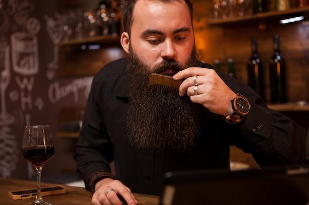 Hipster-barkeeper, der sich um seinen langen bart kümmert. toller bart.
