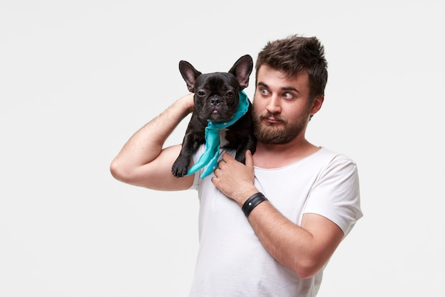 Hipster bearded kerl hält und umarmt einen schönen französischen bulldoggenhund in seinen armen mit liebe und spielt mit ihm