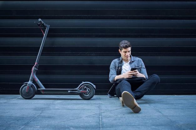 Hipster benutzt ein smartphone, während er neben seinem elektroroller auf dem boden an der schwarzen wand sitzt