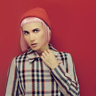 Hipster-blondine mit rotem hut und kariertem mantel mode-vintage-stil