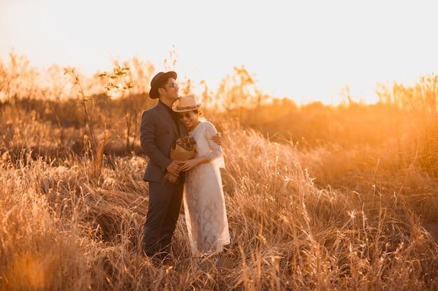 Hipster braut und bräutigam auf dem hügel. paar jungvermählten bei der hochzeit im naturwald, hochzeitspaar bei sonnenuntergang