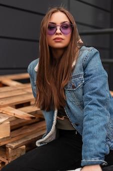 Hipster der jungen frau des modernen porträts in der violetten weinlesebrille in der stylischen blauen vintage-denimjacke in der nähe des grauen gebäudes im freien. hübsches urbanes mädchenmodell ruht auf der stadt. amerikanischer stil.