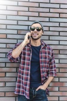 Hipster, der stadtstraße auf backsteinmauerhintergrund anruft. erstaunlicher mann, der smartphone im stehen der intelligenten freizeitkleidung hält. urbaner junger beruflicher lebensstil.