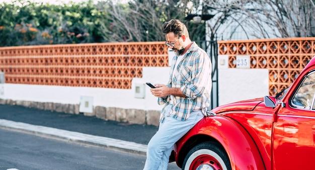 Hipster erwachsener mann, der außerhalb des autos steht und text auf einem modernen telefon - planung von zielreisenden mit mobilfunkverbindung - fahrzeugbesitzer sendet nachricht auf smartphone