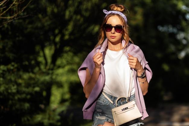 Hipster-frau mit bandana und modischer sonnenbrille in trendigen jeans-shorts mit handtasche und lila sweatshirt im park