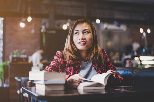 Hipster frau teenager sitzen genießen lesebuch im café. vintage filter getönt.