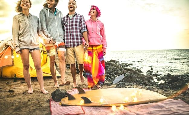 Hipster-freunde, die spaß haben, mit led-neon-laternen auf der strand-camping-party spazieren zu gehen