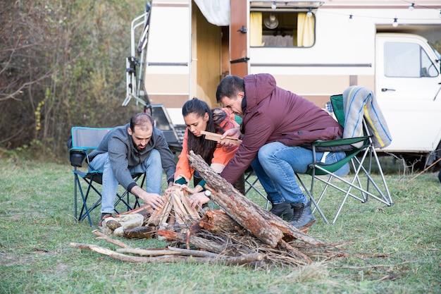 Hipster-freunde machen zusammen ein lagerfeuer im bergwald. freunde, die mit retro-wohnmobil campen.