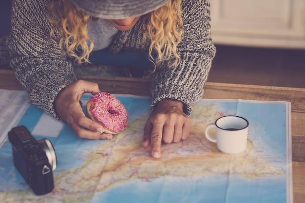 Hipster junge dame beim frühstück und planung der nächsten reise. langes blondes haar und alternativer lebensstil für menschen. reise- und fernwehkonzept