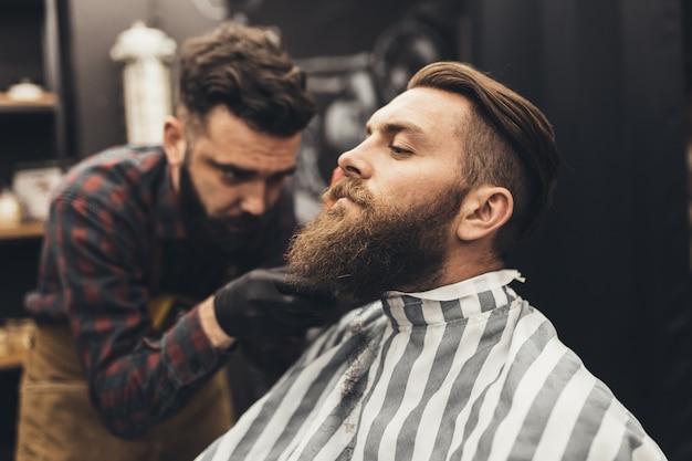 Hipster junger gut aussehender mann, der friseursalon besucht. trendiges und stylisches bartstyling und schnitt.