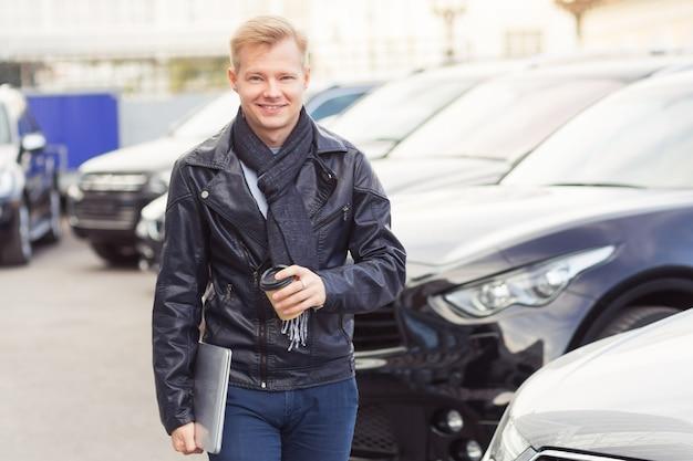 Hipster junger mann zu fuß in der stadt mit laptop in der nähe von autos