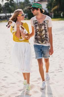 Hipster junges stilvolles hipsterpaar in der liebe, die mit hund im tropischen strand geht und spielt