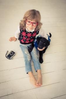 Hipster-kind und hund. kind spielt zu hause