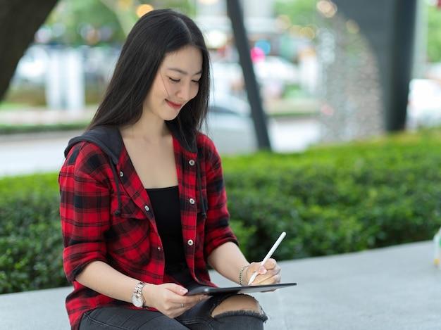 Hipster-künstlerfrau, die sich im park mit digitalem tablet und stylus-stift entspannt, um das stadtbild zu skizzieren
