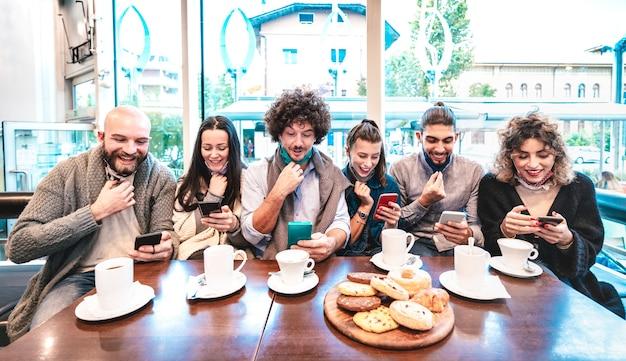 Hipster-leute, die positive nachrichten auf dem mobilen smartphone an der kaffeebar anfeuern