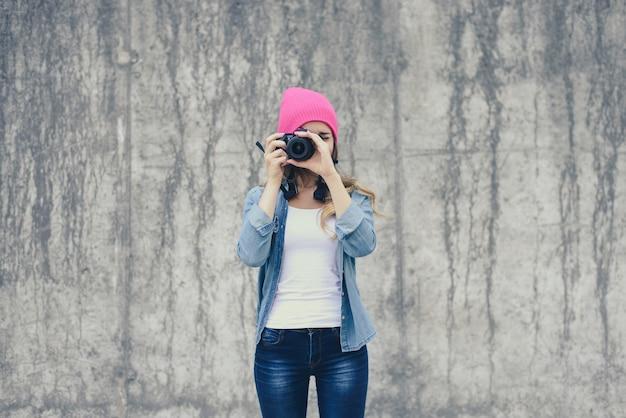 Hipster-mädchen in der jeanskleidung und im rosa hut, die foto gegen graue betonwand nehmen. kamera im fokus