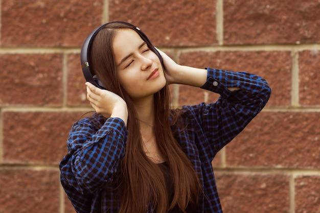 Hipster-mädchen mit kopfhörern auf der straße, die musik hört