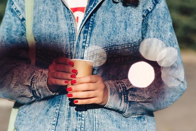 Hipster-mädchen mit pappbecher mit kaffee zum mitnehmen. frau, die tasse in den händen hält.