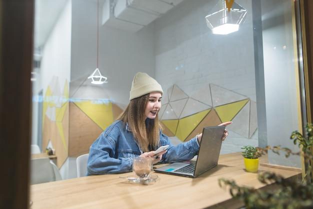 Hipster mädchen sitzt in einem gemütlichen café mit einem laptop und lächelt. porträt eines schönen mädchens durch das fenster des cafés