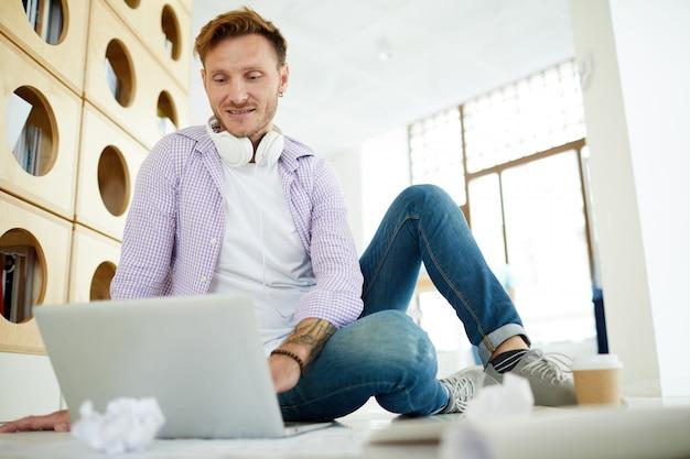 Hipster-mann, der im modernen raum arbeitet