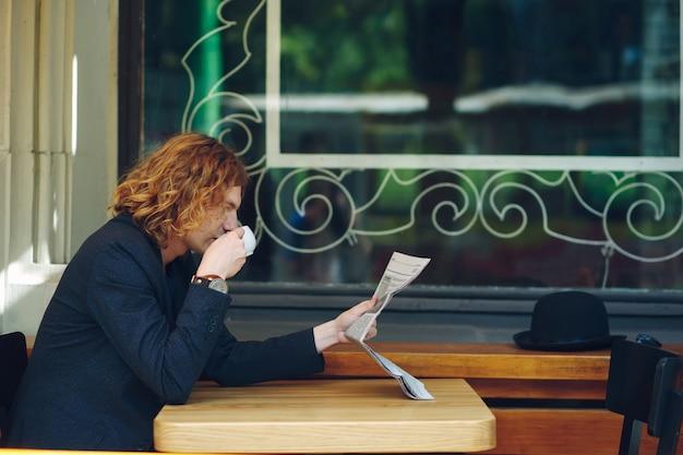 Hipster mann, der kaffee beim lesen trinkt
