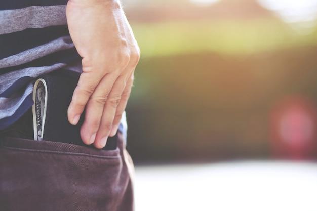 Hipster mann hände halten brieftasche mit kreditkarten und stapel geld