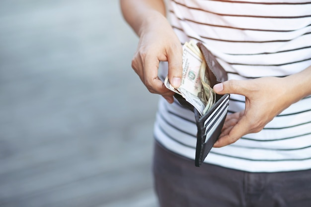 Hipster mann hände halten brieftasche mit kreditkarten und stapel geld.