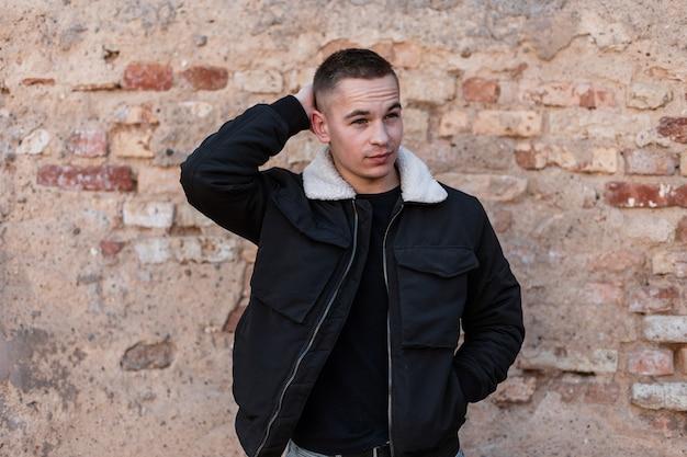 Hipster-mann in modekleidung mit jacke nahe ziegelmauer