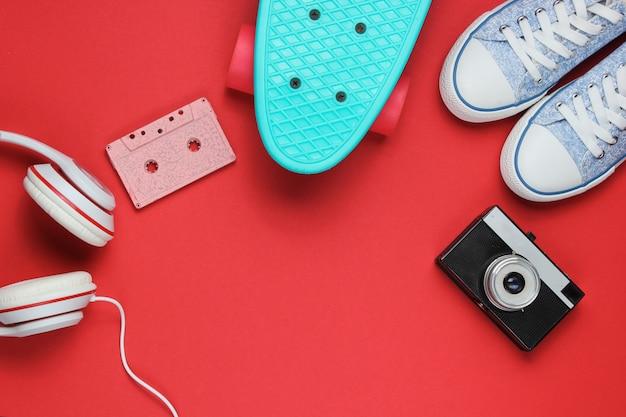 Hipster outfit. skateboard, kopfhörer, audiokassette, turnschuhe, retro-kamera auf rotem hintergrund. kreativer mode-minimalismus. minimaler sommerspaß. pop-art. 80er jahre.
