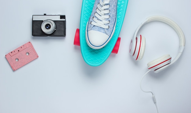 Hipster outfit. skateboard, kopfhörer, audiokassette, turnschuhe, retro-kamera auf weißem hintergrund. kreativer mode-minimalismus. minimaler sommerspaß. pop-art. 80er jahre.