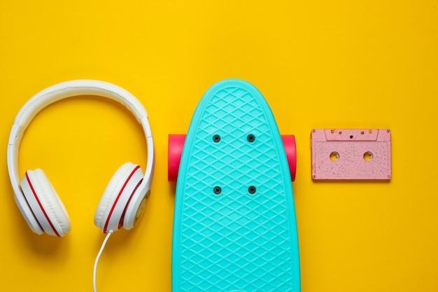 Hipster outfit. skateboard mit kopfhörern, audiokassette auf gelbem hintergrund. kreativer mode-minimalismus. trendiger alter modischer stil. minimaler sommerspaß. pop-art. musikkonzept.