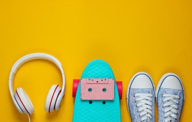Hipster outfit. skateboard mit kopfhörern, audiokassette und turnschuhen auf gelbem hintergrund. kreativer mode-minimalismus. minimaler sommerspaß. pop-art. 80er jahre.