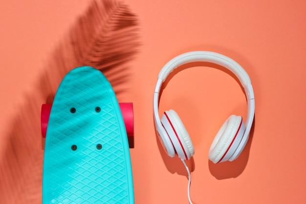 Hipster outfit. skateboard mit kopfhörern auf korallenhintergrund mit schatten vom palmblatt. kreativer mode-minimalismus. trendiger alter modischer stil. minimaler sommerspaß. musikkonzept