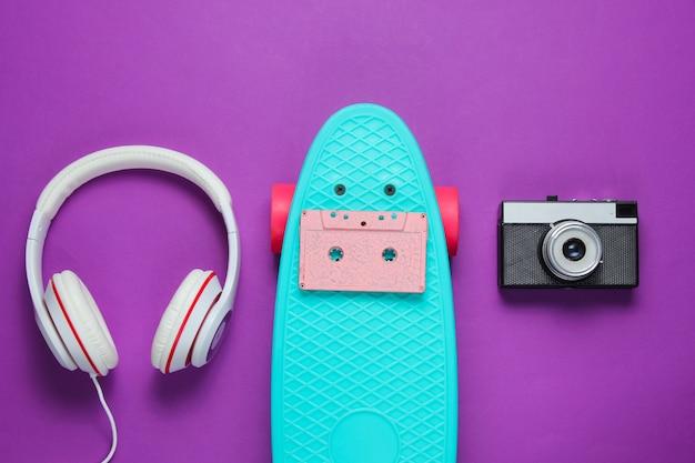 Hipster outfit. skateboard mit kopfhörern, retro-kamera, audiokassette auf lila hintergrund. kreativer mode-minimalismus. trendiger alter modischer stil. minimaler sommerspaß.